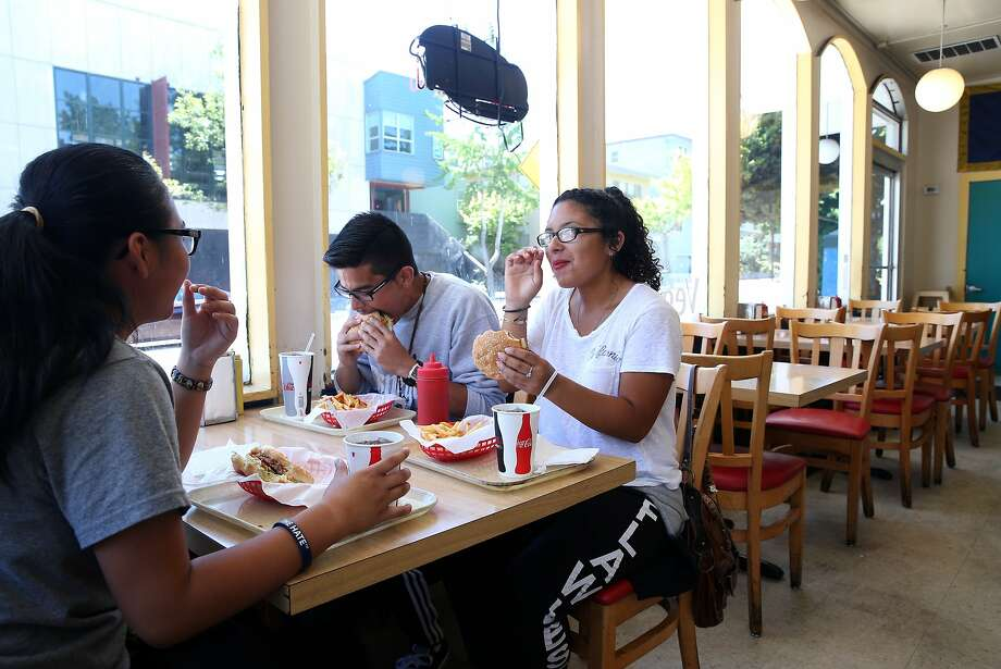 Maria Llose (left), Rigoberto Gonzalez and Jasmine Martinez have lunch at Oscar's in Berkeley, Calif. on Friday, July 3, 2015. Located just a few blocks south of the Gourmet Ghetto, the popular hamburger joint that has been serving charbroiled burgers and french fries since 1950 is shutting down at the end of the summer, according to the owner. Photo: Paul Chinn, The Chronicle
