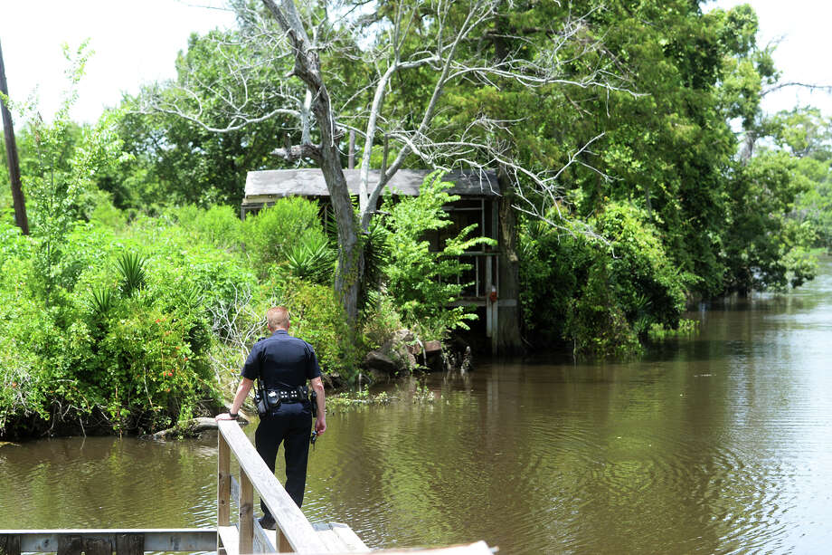 Lt. James Davis looks off the dock at Burkart's Marina on Friday. Tommie Woodward, 28, was attacked and killed by an alligator while swimming in Adams Bayou at Burkart's Marina early Friday morning. The incident was the first fatal attack by an alligator in Texas in about 200 years. Photo taken Friday 7/3/15 Jake Daniels/The Enterprise Photo: Jake Daniels / Jake Daniels/The Enterprise / ©2015 The Beaumont Enterprise/Jake Daniels