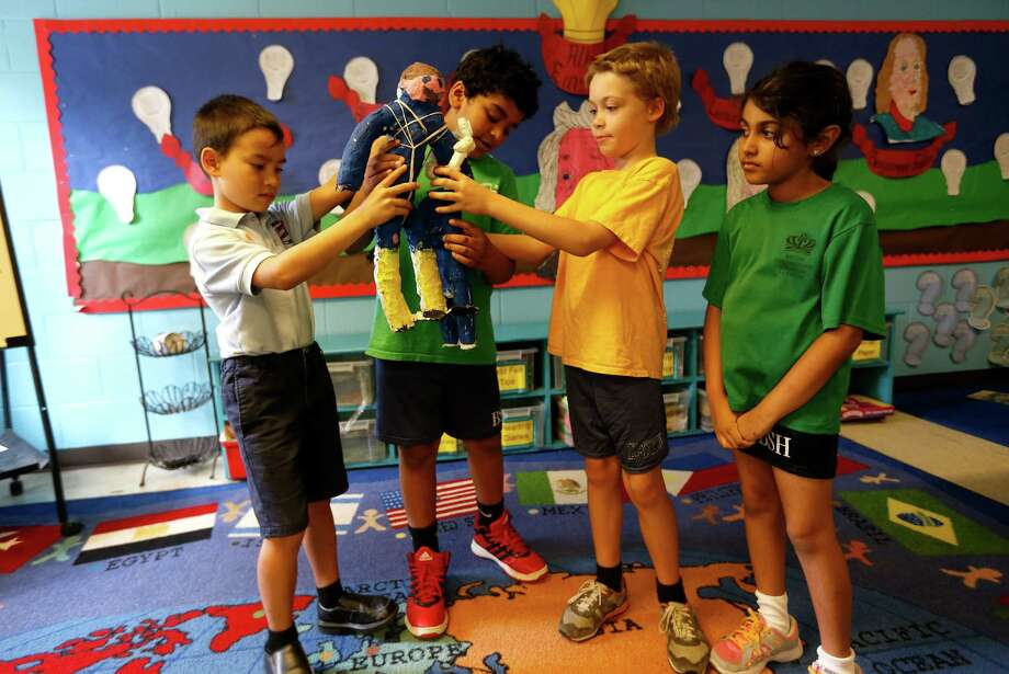"""Erick Drew, 8, Adam Ali, 7, Oscar Case, and Aaniyah Bhola, both 8, British International School third graders, demonstrate their Air Crutch. The group participated and won """"Best Pitch"""" for their Air Crutch invention at the Texas Medical Center's first Young Inventor contest, last week.  Photographed in their classroom, Tuesday, June 30, 2015, in Houston.  ( Karen Warren / Houston Chronicle ) Photo: Karen Warren, Staff / © 2015 Houston Chronicle"""