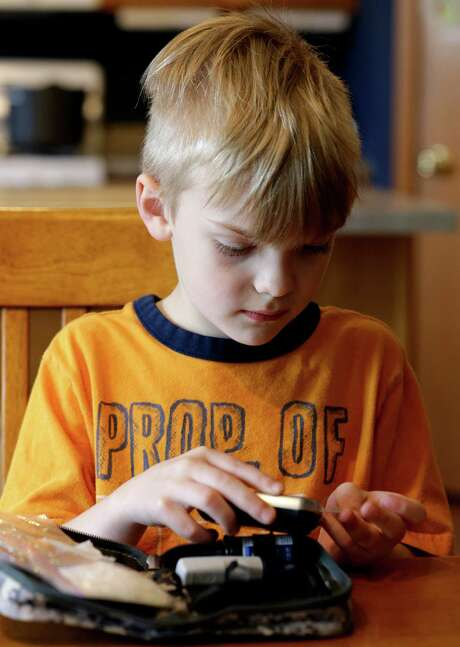 In this photo taken Wednesday, May 13, 2015, Weston Murphy, 5, who has Type 1 diabetes, pricks his finger to test his blood at his home in Plainfield, Ill. His oldest brother is among more than 400 children and adults participating in U.S. government-funded international research investigating whether experimental insulin capsules can prevent or at least delay Type 1 diabetes. (AP Photo/Nam Y. Huh) Photo: Nam Y. Huh, STF / Associated Press / AP