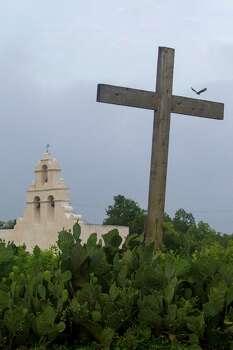 A bird flies over a wood cross at Mission San Juan Capistrano in San Antonio, Texas. Ray Whitehouse / San Antonio Express-News Photo: Ray Whitehouse, Staff / San Antonio Express-News / 2015 San Antonio Express-News