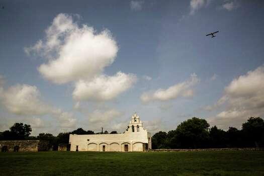 A plane flies over Mission San Juan Capistrano in San Antonio, Texas. Ray Whitehouse / San Antonio Express-News Photo: Ray Whitehouse, Staff / San Antonio Express-News / 2015 San Antonio Express-News