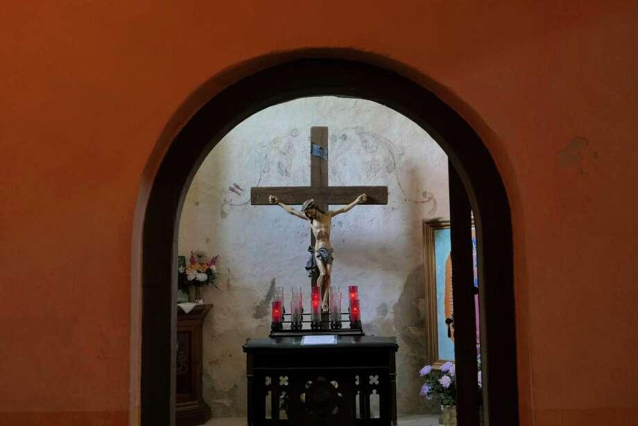 A crucifix adorns a small room in Mission Nuestra Señora de la Purisima Concepción de Acuña, known simply as Mission Concepcion. Photo: Billy Calzada, Staff / San Antonio Express-News / San Antonio Express-News