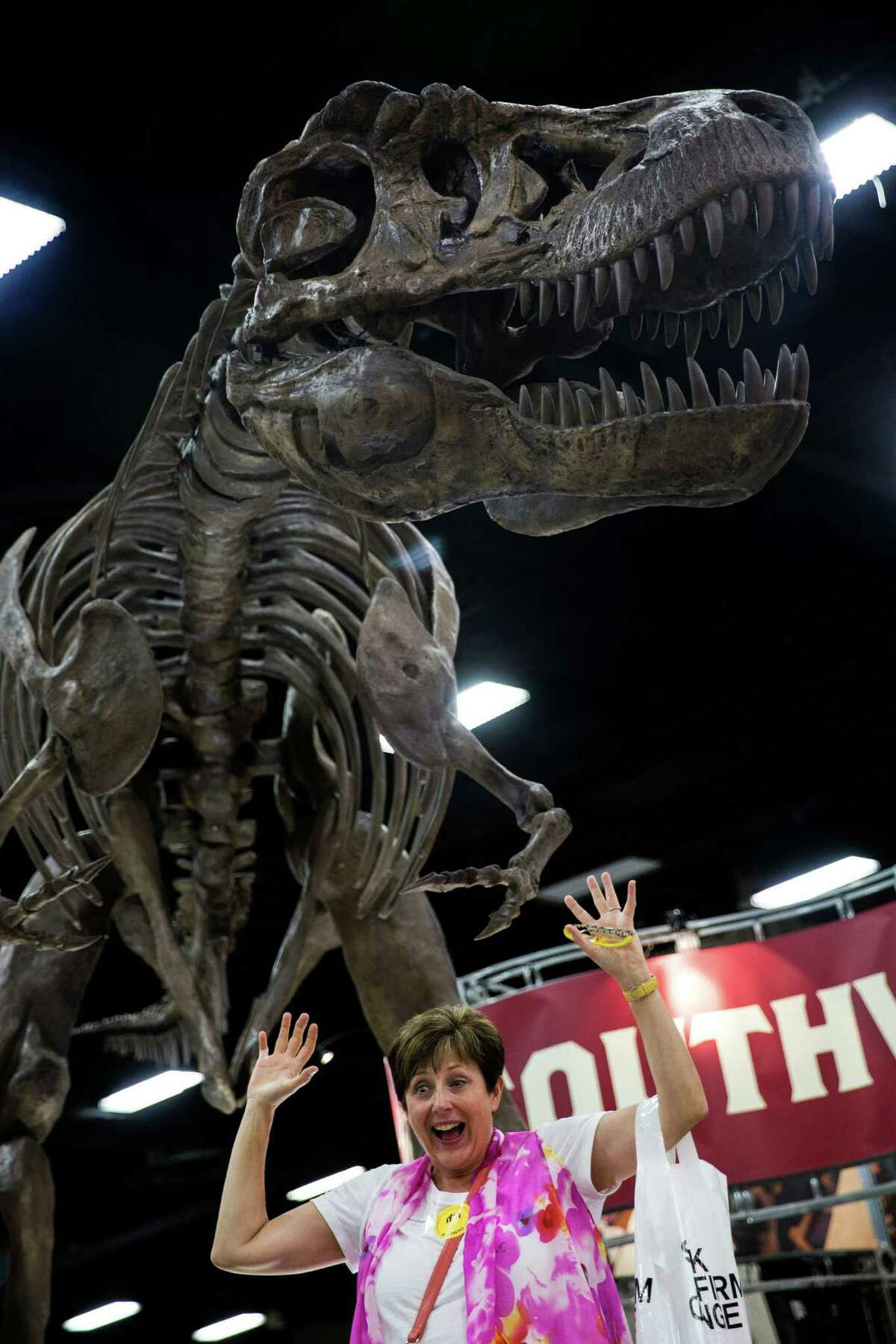 Inside the Henry B. Gonzalez Convention Center, Mary King of Chattanooga, Tennessee, poses for a picture with a model of a dinosaur at The 60th General Conference Session of the Seventh-day Adventist Church in San Antonio, Texas. Ray Whitehouse / San Antonio Express-News