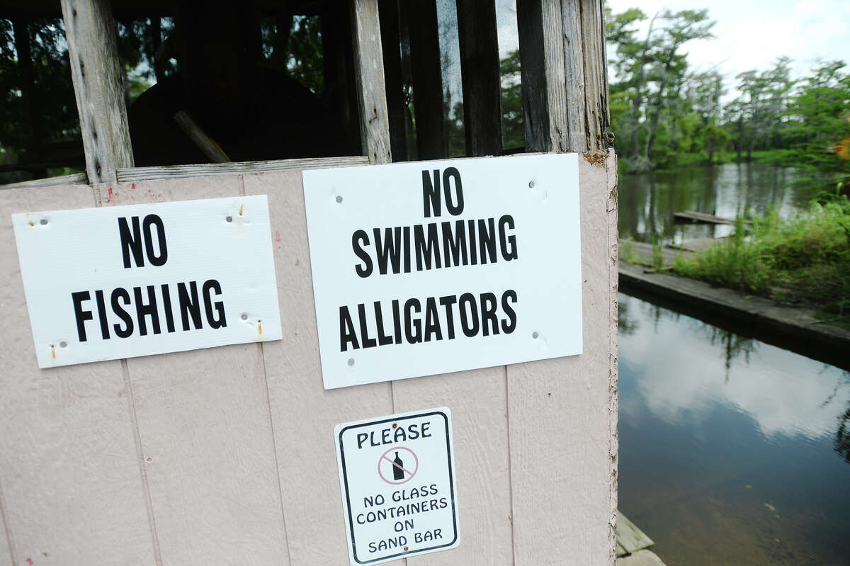 Signs warning patrons not to swim in Adams Bayou are seen at Burkart's Marina on Friday. Tommie Woodward, 28, was attacked and killed by an alligator while swimming in Adams Bayou at Burkart's Marina early Friday morning. The incident was the first fatal attack by an alligator in Texas in about 200 years. Photo taken Friday 7/3/15 Jake Daniels/The Enterprise