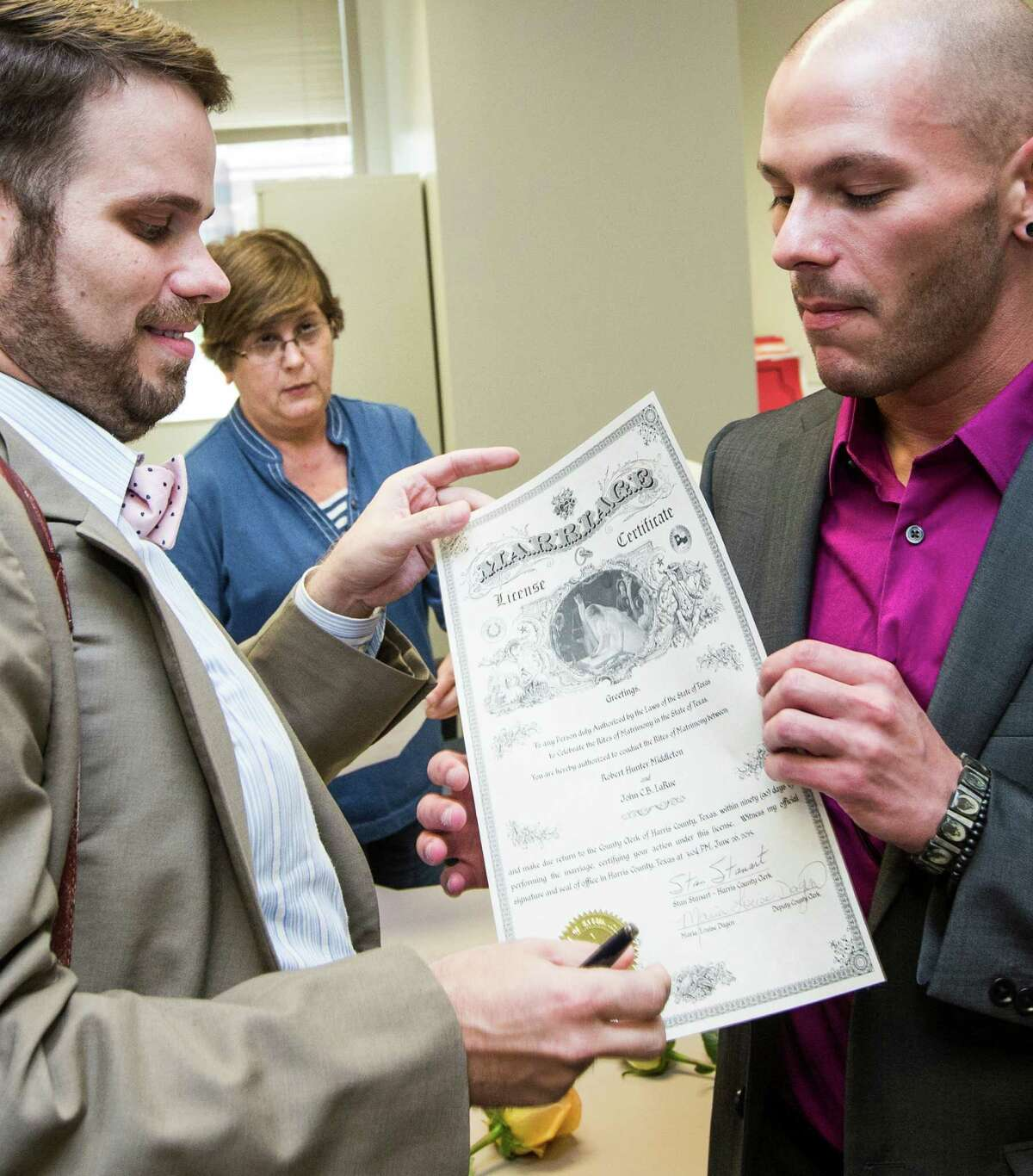 Before issuing a marriage license to John LaRue, left, and Hunter Middleton, Maria Dagen told them her daughter and daughter-in-law were proud of the historic role she played in Harris County.