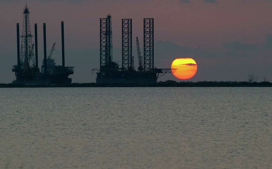 The sun sets behind twooffshore oil platform rigs in Port Fourchon, Louisiana. The new period of cheap oil and ample supplies brought about by the boom in U.S. shale production has raised a prospect unthinkable as recently as a few months ago — that the world no longer needs all the big, expensive projects planned by companies including Shell, Total and Exxon. Photo: AFP / Getty Images File Photo / AFP