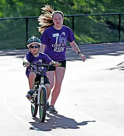 Andrew Graziano gets a little assist from volunteer Morgan Adams during the I Can Ride Bike Camp at Union College Friday morning, July 3, 2015, in Schenectady, N.Y.  The I Can Ride Bike Camp is designed to take special needs youths and teach them to ride bikes.   (Skip Dickstein/Times Union) Photo: SKIP DICKSTEIN / 00032483A