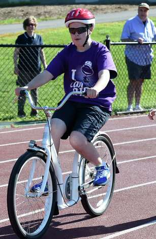 Matthew Miller peddles past his parents Cheryl and John Miller of Scotis (background right) under his own power during the I Can Ride Bike Camp at Union College Friday morning, July 3, 2015, in Schenectady, N.Y.  The I Can Ride Bike Camp is designed to take special needs youths and teach them to ride bikes.   (Skip Dickstein/Times Union) Photo: SKIP DICKSTEIN / 00032483A