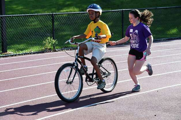 Kristian Fields, 10, of Schenectady gets some assistance from a volunteer during the I Can Ride Bike Camp at Union College Friday morning, July 3, 2015, in Schenectady, N.Y.  The I Can Ride Bike Camp is designed to take special needs youths and teach them to ride bikes.   (Skip Dickstein/Times Union) Photo: SKIP DICKSTEIN / 00032483A