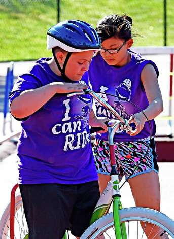 Troy Scott, left, gets some individual assistance from volunteer Maddie Montayne during the I Can Ride Bike Camp at Union College Friday morning, July 3, 2015, in Schenectady, N.Y.  The I Can Ride Bike Camp is designed to take special needs youths and teach them to ride bikes.   (Skip Dickstein/Times Union) Photo: SKIP DICKSTEIN / 00032483A