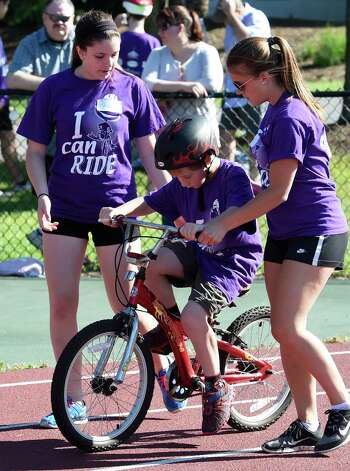 Paige Bailey, left, and Kim Denny, right assist Addison Hine with his peddling during the I Can Ride Bike Camp at Union College Friday morning, July 3, 2015, in Schenectady, N.Y.  The I Can Ride Bike Camp is designed to take special needs youths and teach them to ride bikes.   (Skip Dickstein/Times Union) Photo: SKIP DICKSTEIN / 00032483A