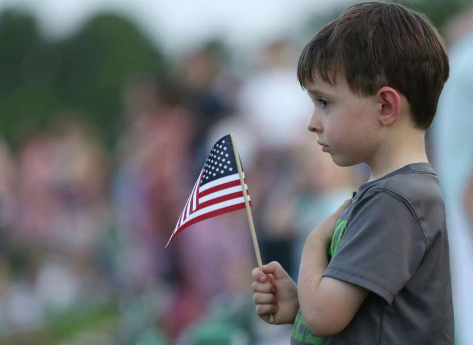 Jackson Neunuebel, 5, holds a flag as the national anthem is performed to begin the Star-Spangled Salute at the Cynthia Woods Mitchell Pavilion Thursday, July 2, 2015, in The Woodlands. Photo: Jon Shapley, Houston Chronicle / © 2015 Houston Chronicle