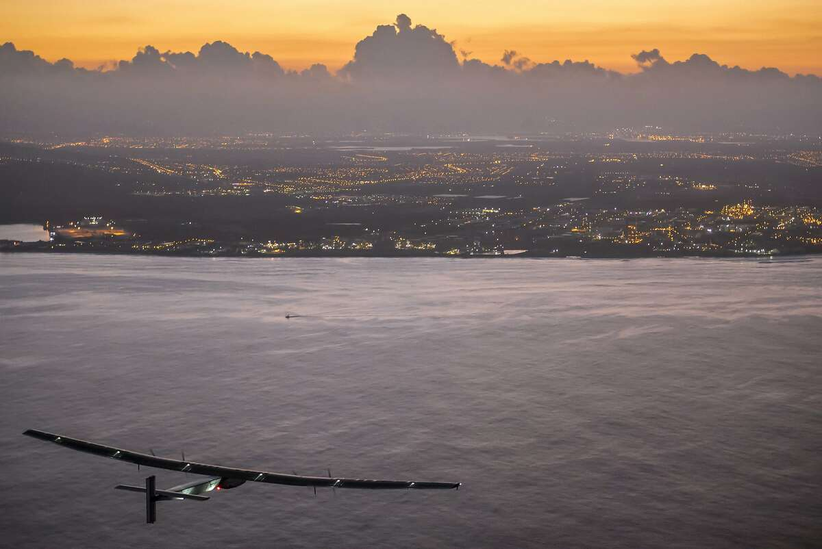 In this photo provided by Jean Revillard, Solar Impulse 2, a plane powered by the sun's rays and piloted by Andre Borschberg, approaches Kalaeloa Airport near Honolulu, Friday, July 3, 2015. His voyage from Nagoya, Japan broke the record for the world's longest nonstop solo flight, his team said. (Jean Revillard/Global Newsroom via AP)