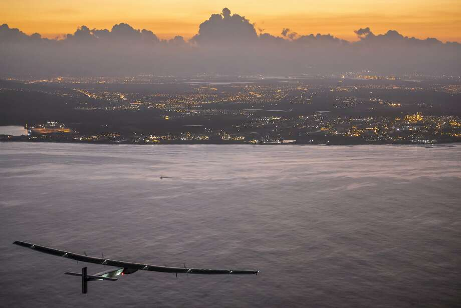 In this photo provided by Jean Revillard, Solar Impulse 2, a plane powered by the sun's rays and piloted by Andre Borschberg, approaches Kalaeloa Airport near Honolulu, Friday, July 3, 2015. His voyage from Nagoya, Japan broke the record for the world's longest nonstop solo flight, his team said. (Jean Revillard/Global Newsroom via AP) Photo: Jean Revillard, Associated Press