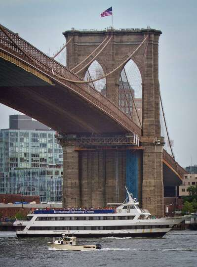 A NYPD harbor boat travels under the Brooklyn Bridge as it patrols near the East River staging area