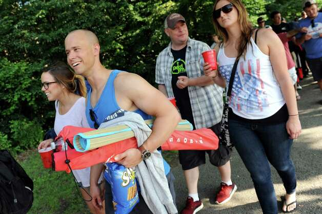 Amy Fagundes of Providence, R.I., left, and her boyfriend Mike Giammarco, center, carry items to claim their spot on the lawn for the Dave Matthews Band show on Friday, July 3, 2015, at Saratoga Performing Arts Center in Saratoga Springs, N.Y. (Cindy Schultz / Times Union) Photo: Cindy Schultz / 00032321A