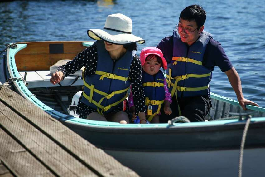 A family rides in a wooden boat during the 39th annual Lake Union Wooden Boat Festival. The free annual event celebrates the maritime heritage of the Northwest, offering tours, music and rides on the water in historic wooden boats. The festival continues through July 5th at Lake Union Park and the Center for Wooden Boats.