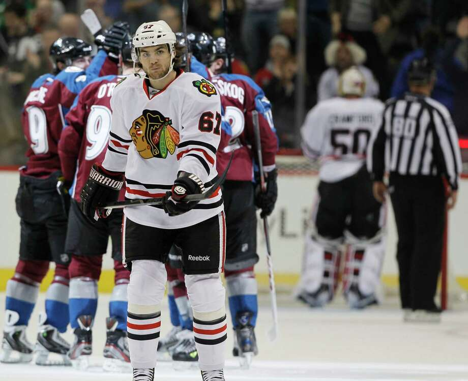 As members of the Colorado Avalanche, back, celebrate a goal by Ryan O'Reilly, Chicago Blackhawks right wing Michael Frolik (67), of the Czech Republic, skates back to the bench in the second period of an NHL hockey game in Denver, Friday, March 8, 2013. (AP Photo/David Zalubowski) Photo: David Zalubowski, STF / AP