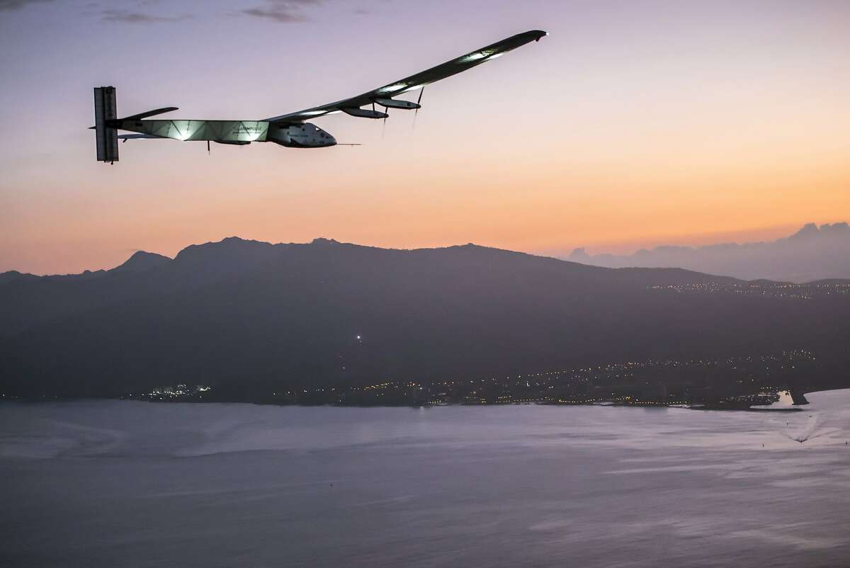Solar Impulse 2, a plane powered by the sun's rays and piloted by Andre Borschberg, approaches Kalaeloa Airport near Honolulu, Friday, July 3, 2015. His 120-hour voyage from Nagoya, Japan broke the record for the world's longest nonstop solo flight, his team said. (Jean Revillard/Global Newsroom via AP)