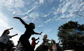 Kids rush to pop bubbles made by Eddie Dilworth III on the Augusta Common during First Friday, Friday, July 3, 2015, in Augusta, Ga. Dilworth managed to create bubbles over ten feet in length, utilizing two walking poles, some rope and a bucket of soapy liquid. (Todd Bennett/The Augusta Chronicle via AP)