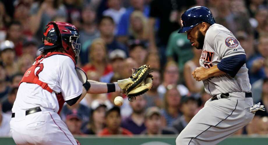 Boston Red Sox catcher Ryan Hanigan, left, can't make the catch on a wide throw by left fielder Hanley Ramirez as Houston Astros designated hitter Jon Singleton scores on a double by Jason Castro during the fourth inning of a baseball game at Fenway Park in Boston, Friday July 3, 2015. (AP Photo/Charles Krupa) Photo: Charles Krupa, STF / AP