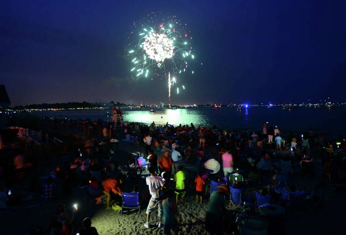 Hundreds of spectators watch the holiday fireworks display at Penfield and Jennings beaches in Fairfield on Friday.