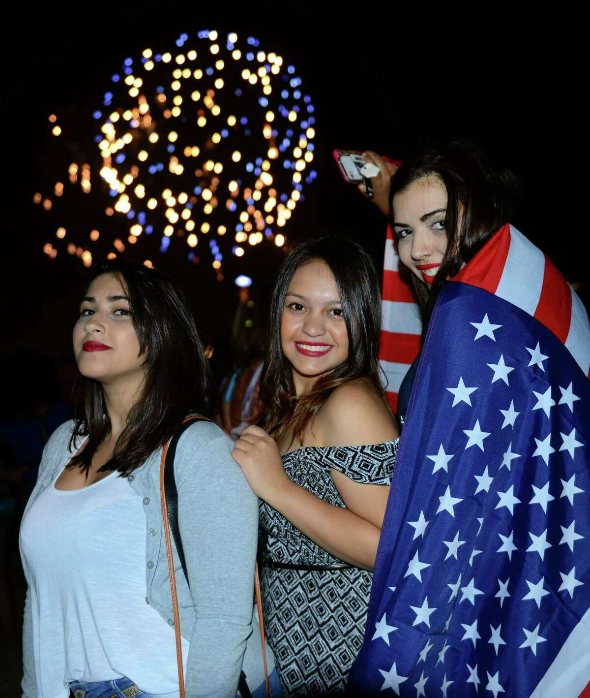 Darien residents Rafaella Gaiao, left, Daiane Cristina Marques dos Santos, center, and Camila Petrovich, pose for a photo during the holiday fireworks show at Penfield and Jennings Beaches in Fairfield, Conn., on Friday July 3, 2015.