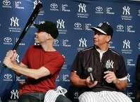 Zack Hample, left, examines an autographed bat given to him by Alex Rodriguez after Hample presented Rodriguez with the baseball on which Rodriguez got his 3,000th career hit during a news conference, Friday, July 3, 2015, in New York. Hample caught the ball, which was a solo home run to right field on Friday, June 19, against the Detroit Tigers. (AP Photo/Julie Jacobson)  ORG XMIT: NYJJ110