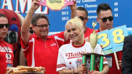 Miki Sudo, second from right, holds her trophy and smiles after winni