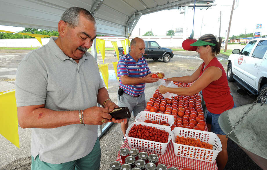 Chuck Gradney, left, and Kirk Conner purchase tomatoes from Kathy Morvan at the Doherty produce stand on Wednesday. Photo taken Wednesday, July 01, 2015 Guiseppe Barranco/The Enterprise Photo: Guiseppe Barranco, Photo Editor
