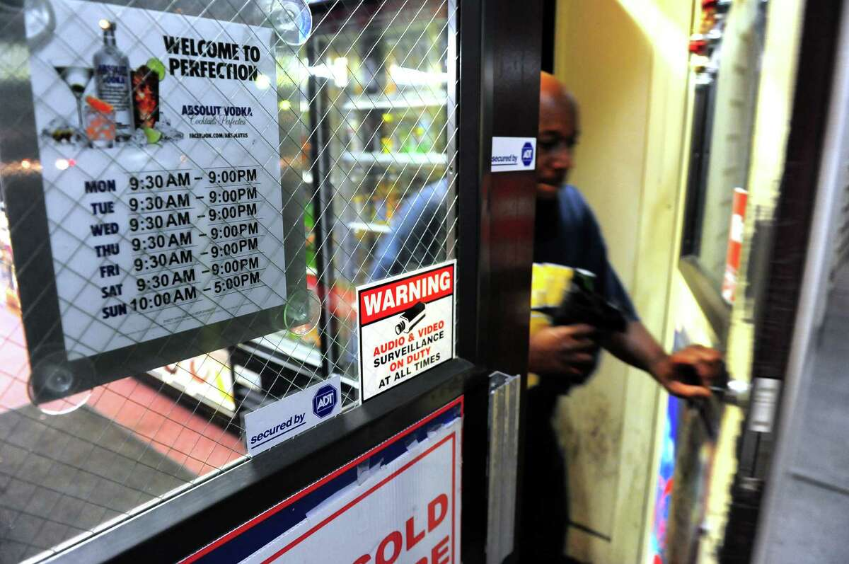A customers exits Julianne's Wines & Liquors in Bridgeport, Conn., on Thursday July 2, 2015. A new state law lets liquor stores stay open until 10 p.m. if they want to, instead of 9 p.m. Note the placard with the store's old hours at left.