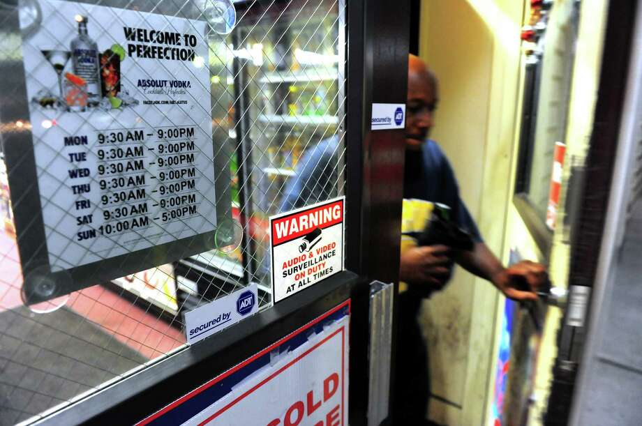 A customers exits Julianne's Wines & Liquors in Bridgeport, Conn., on Thursday July 2, 2015. A new state law lets liquor stores stay open until 10 p.m. if they want to, instead of 9 p.m. Note the placard with the store's old hours at left. Photo: Christian Abraham / Hearst Connecticut Media / Connecticut Post