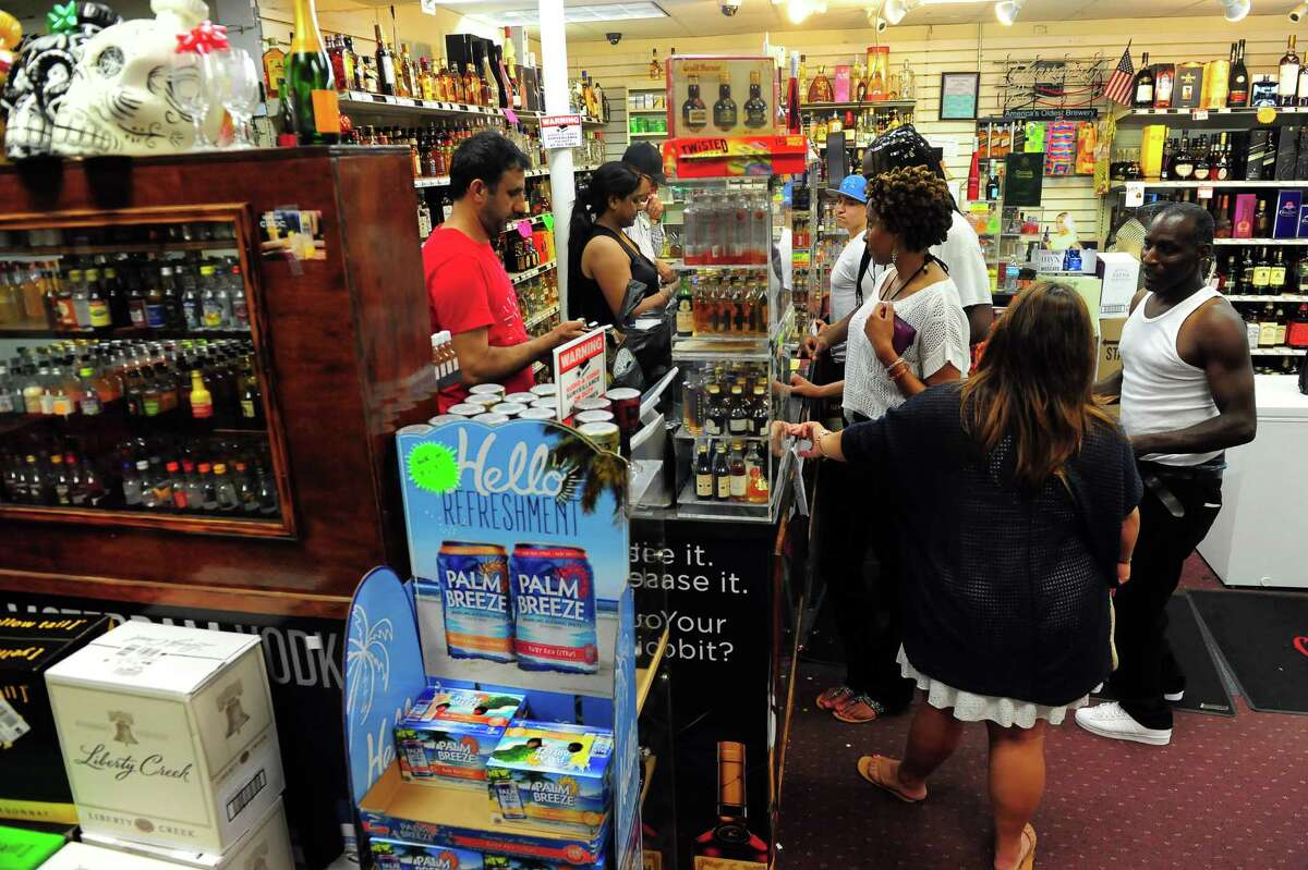 A last minute rush of customers buy from Julianne's Wines & Liquors in Bridgeport, Conn., on Thursday July 2, 2015. A new state law lets liquor stores stay open until 10 p.m. if they want to, instead of 9 p.m.