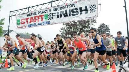 Runners start the John Demille 50th Annual Firecracker 5K and 10K road races on School Street in Bethel. Saturday, July 4, 2015