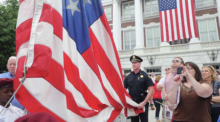 Greenwich Police Lt. Richard Cochran holds the American Flag as the Boys & Girls Club of Greenwich Honor Guard begins the flag raising during the Fourth of July Ceremony at Greenwich Town Hall in Greenwich, Conn., Saturday morning, July 4, 2015. The Independence Day Association of Greenwich sponsored the annual event.