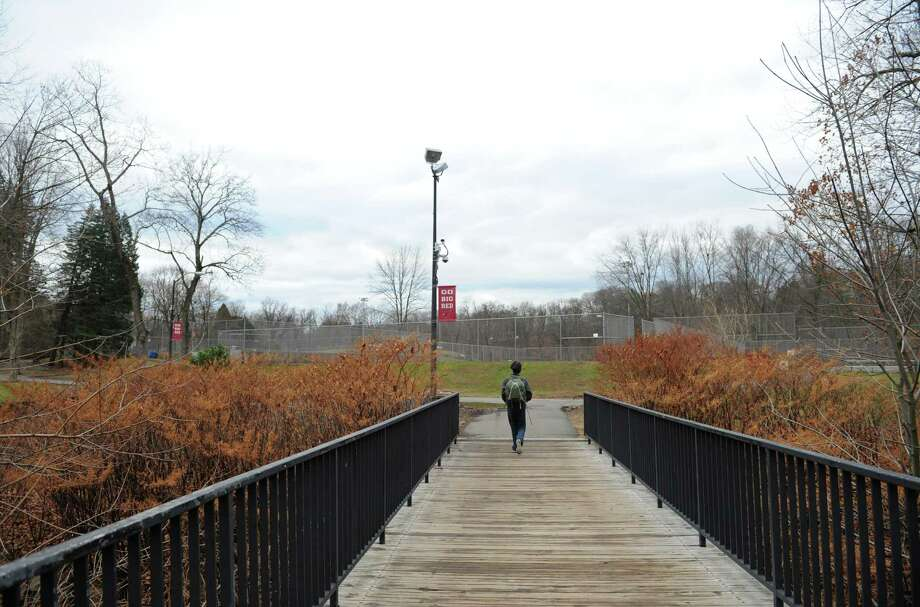 A student walks across a bridge leading to the athletic fields at Greenwich High School in December 2014. PCBs and other toxins have been found in soil under the playing fields and other grassy areas. The school is off-limits this summer as clean-up work gets under way. Photo: Tyler Sizemore / Tyler Sizemore / Greenwich Time