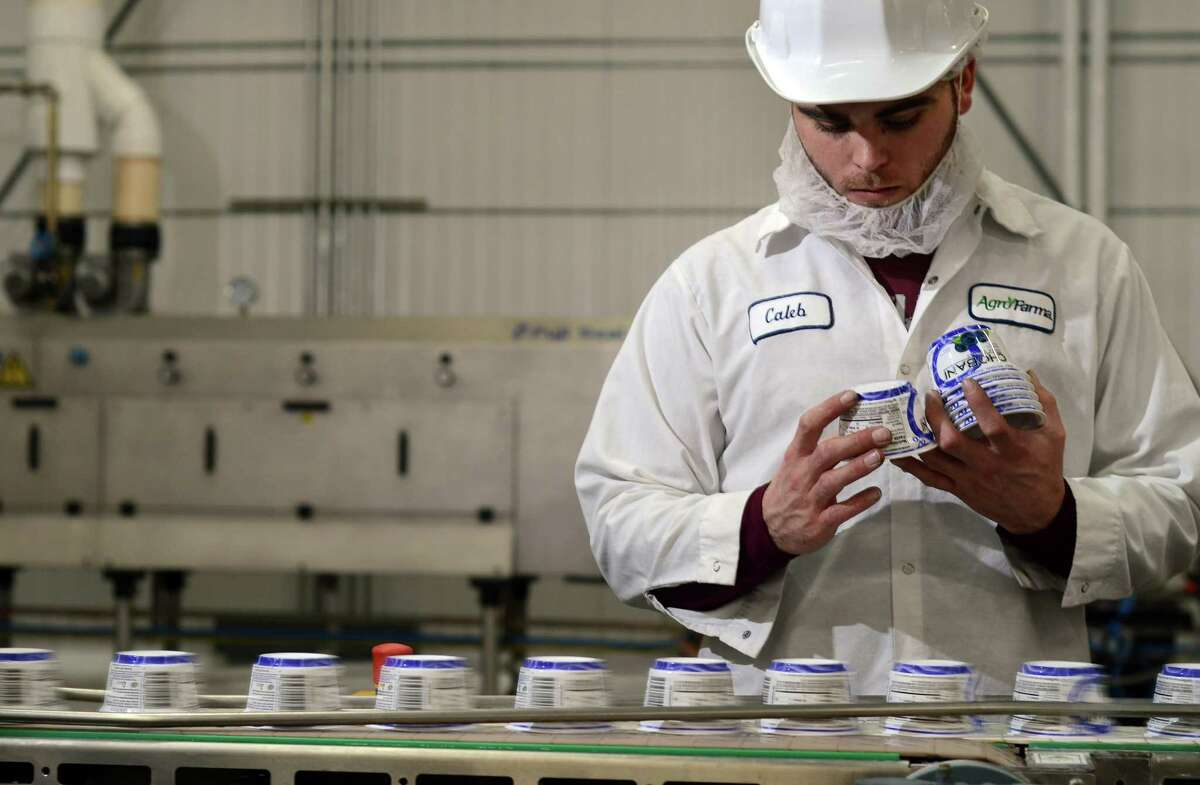 Caleb Odell inspects yogurt containers at the Chobani plant in New Berlin, N.Y., Dec. 29, 2011. (Heather Ainsworth/The New York Times)
