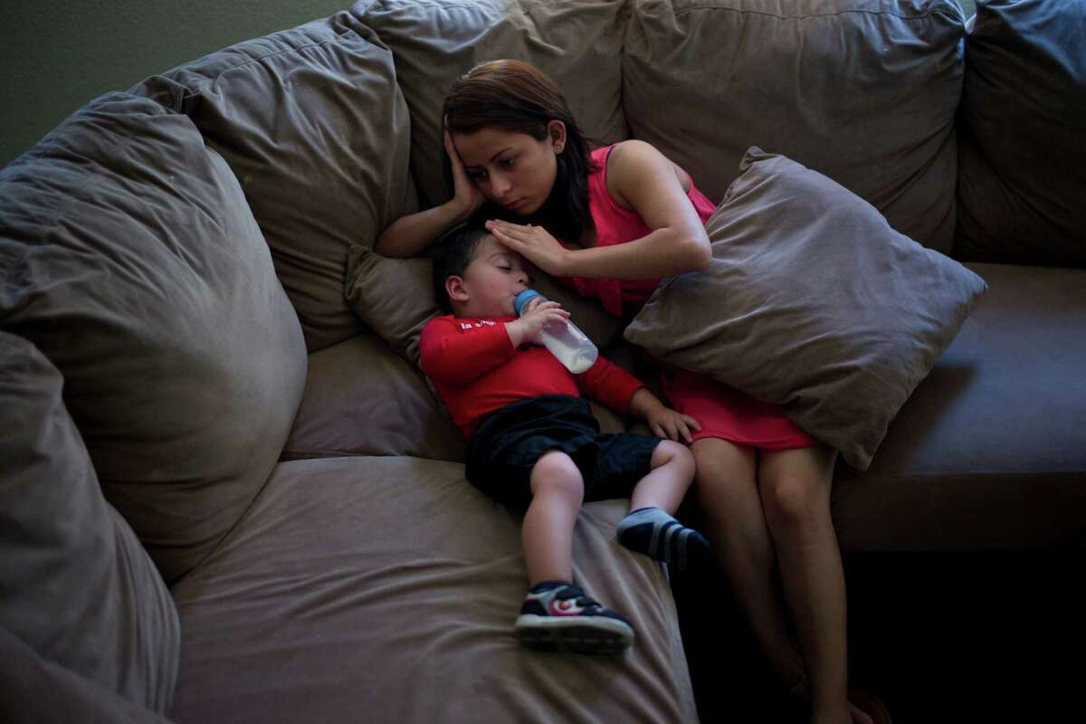 In this Monday, June 8, 2015 photo, 1-year-old Joshua Tinoco snuggles with his mother, Dunia Bueso, a 18-year-old Honduran who won the right to seek permanent residency under a U.S. program for abused and abandoned children, while taking a nap at their relative's home in Los Angeles. At a brief hearing, a government lawyer tells the teenage mother that her son is an immigration enforcement priority for the United States and should be sent back to his native Honduras even though she is being allowed to stay and seek a green card. (AP Photo/Jae C. Hong) ORG XMIT: CAJH205