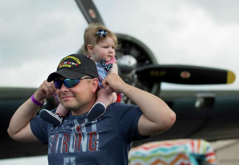 Army captain Tim Souza walks with his 7-month-old daughter, Emma, on his shoulders during the Commemorative Air Force Independence Day air show, Saturday, July 4, at Stinson Municipal Airport. Photo: Photos By Darren Abate / For The San Antonio Express-News