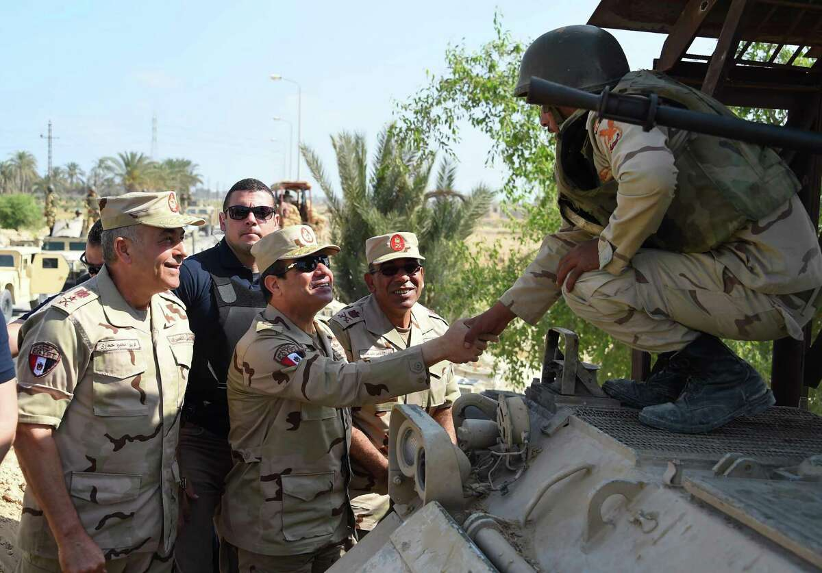 In this picture provided by the office of the Egyptian Presidency, Egyptian President Abdel-Fattah el-Sissi, center, greets members of the Egyptian armed forces in Northern Sinai, Egypt, Saturday, July 4, 2015. Egyptian President Abdel-Fattah el-Sissi has traveled to the troubled northern part of the Sinai Peninsula to inspect troops, after Islamic State-linked militants struck a deadly blow against the military this week in a coordinated assault. (Egyptian Presidency /Mohammed Abdel-Muati via AP) ORG XMIT: CAIBS305