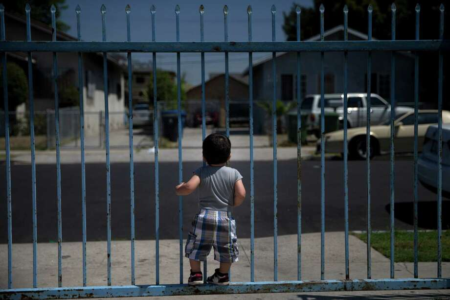 In this Monday, June 8, 2015 photo, 1-year-old Joshua Tinoco clings to a gate at his relative's home in Los Angeles. At a brief hearing, a government lawyer tells his teenage mother that her son is an immigration enforcement priority for the United States and should be sent back to his native Honduras even though she is being allowed to stay and seek a green card. (AP Photo/Jae C. Hong) Photo: Jae C. Hong, STF / Associated Press / AP