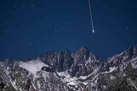 A bright Geminid meteor falls from the sky over Mount Whitney