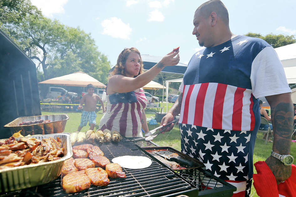 TJ (left) and Chris Bustamante enjoy barbecue Saturday July 4, 2015 during San Antonio's Official 4th of July Celebration & Fireworks Extravaganza held at Woodlawn Lake Park.