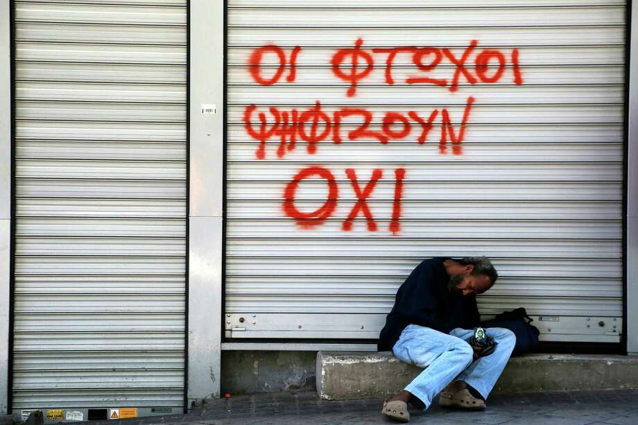 """A man sleeps, holding an icon of Jesus Christ, outside a closed shop with spray paint reading """"Poor vote """"NO"""" in central Athens, on Saturday, July 4, 2015. Whether Greeks decide in Sunday's referendum to accept their lenders' bailout deal or reject it, the government's hold on power may be shakier than its brash prime minister has calculated, analysts say. (AP Photo/Petros Karadjias) Photo: Petros Karadjias, STF / AP"""