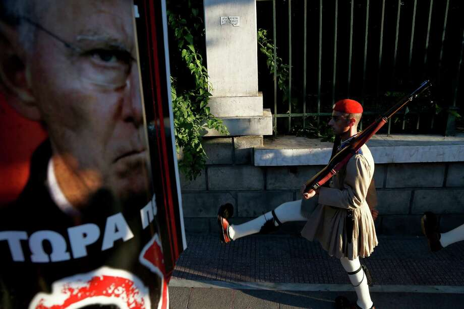An Evzone of the presidential guard passes by a poster of German Finance Minister Wolfgang Schaeuble reading ''For five years he is drinking your blood, now tell him NO'' in central Athens, on Saturday, July 4, 2015. Whether Greeks decide in Sunday's referendum to accept their lenders' bailout deal or reject it, the government's hold on power may be shakier than its brash prime minister has calculated, analysts say. (AP Photo/Petros Karadjias) Photo: Petros Karadjias, STF / AP