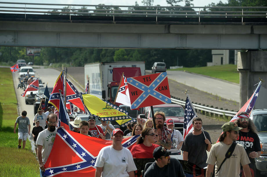 Supporters of the Confederate flag, including members of the regional chapters of Sons of Confederate Veterans, march up Highway 327 in Silsbee on Saturday. Organized by Ricky Stuart, the event, like a similar one at Gulfgate Mall, was intended to celebrate the pride in heritage associated with the flag, and comes in the wake of recent calls to ban the flag.  Photo: Kim Brent / Beaumont Enterprise