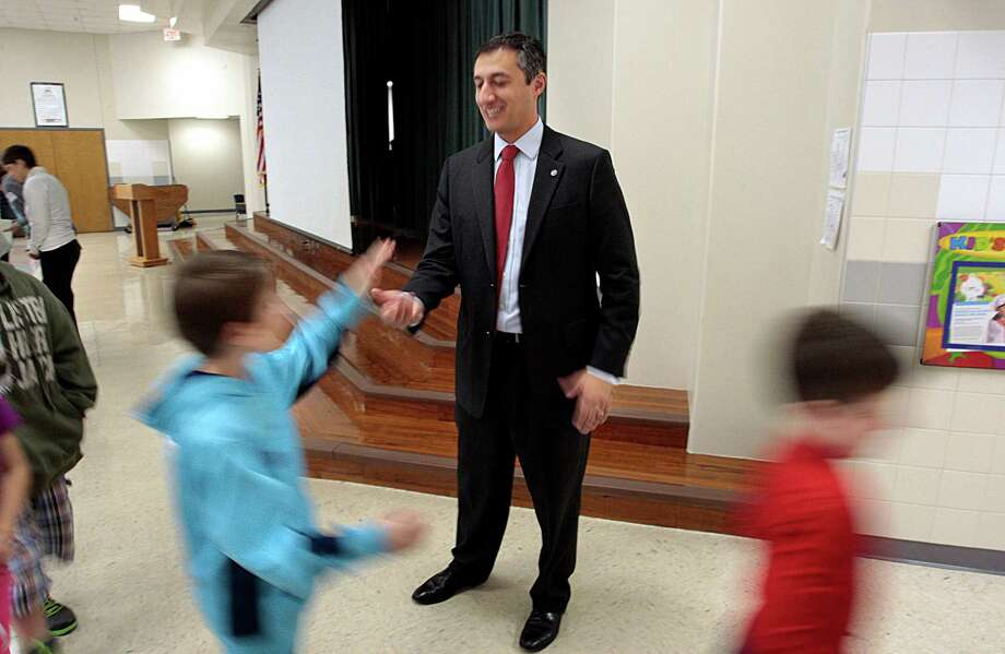FILE - In this Jan. 31, 2014 file photo,Texas State Representative Giovanni Capriglione gives high-fives after speaking to second-grade students at Keller-Harvel Elementary in Keller, Texas. Capriglione authored a bill passed by the Texas legislature to start keeping its gold holdings within in its own borders. But what makes sense politically in such a sovereignty-loving place is creating a logistical conundrum. The law doesn't say where the depository would be or how it should be built or secured.  (Ian McVea/ The Fort Worth Star-Telegram via AP, File) Photo: Ian McVea, MBI / The Fort Worth Star-Telegram