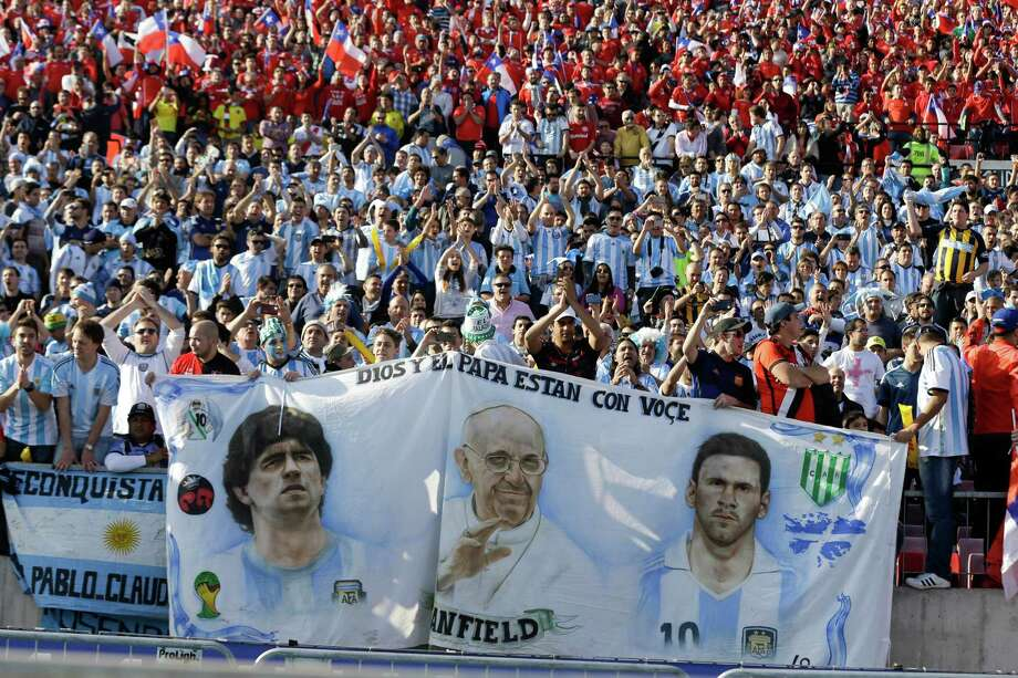 Argentine fans hold images of their favorite sons, soccer star Lionel Messi (right), Pope Francis (center) and  soccer legend Diego Maradona, during the final Copa America soccer match between Argentina and Chile in Santiago, Chile, on Saturday. Photo: Ricardo Mazalan /Associated Press / AP