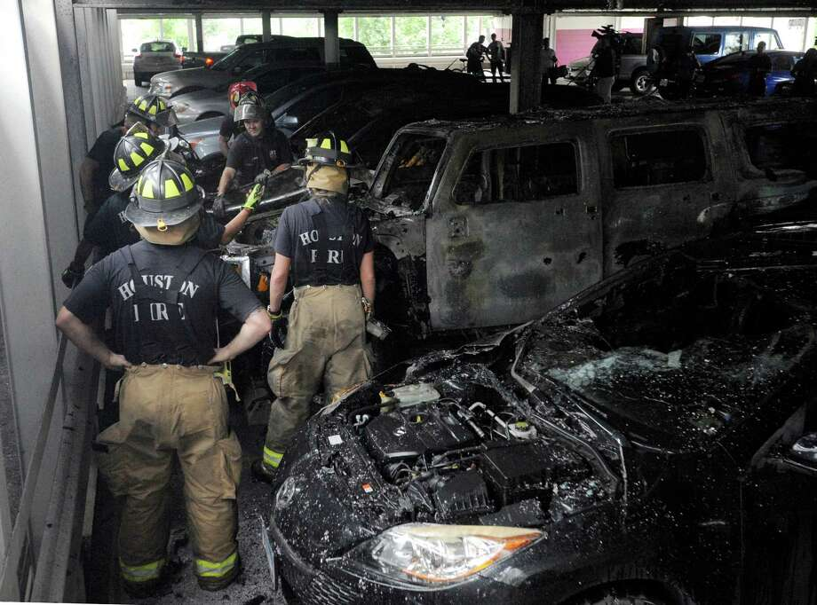 Houston firefighters, shown here working to extinguish a three-car fire in a parking garage in May, are among the city workers whose current pension benefits plan presents a challenge to the city's budget. Photo: Jon Shapley, Staff / © 2015 Houston Chronicle